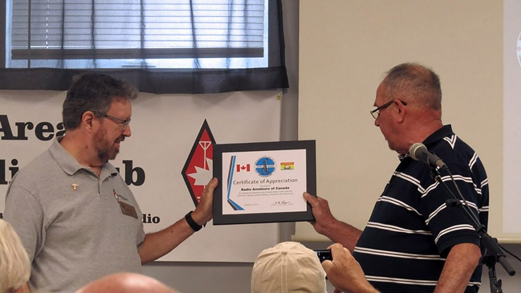 Glenn MacDonell, VE3XRA (RAC President) accepts Certificate of Appreciation from André Goguen, VE9ARG (Moncton Area ARC President) at the RAC Annual General Meeting in Moncton.